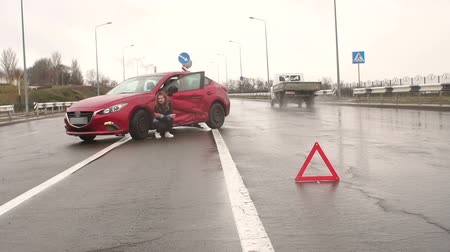 треугольник : Young scared girl standing on the road near the broken car, she was in a car accident and waiting for help. Next to the car is a warning sign of an emergency stop.