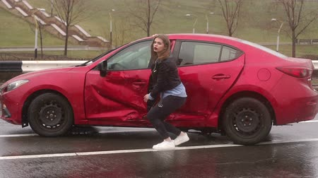 istek : Teen girl smashed her parents car on a wet road, she examines the damage on the door and crying. Car accident on wet road in bad weather. Slow motion. Stok Video