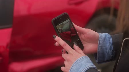 karetka : Close-up of the girl taking pictures on the phone the car that was in an accident on the road. The girl takes pictures of the broken car for the insurance company. Wideo