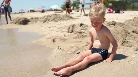 crowded people : Little cute boy sitting on the sand by the sea in the sun, little waves beating against the babys feet. Portrait of a five-year-old boy on the beach in the summer.