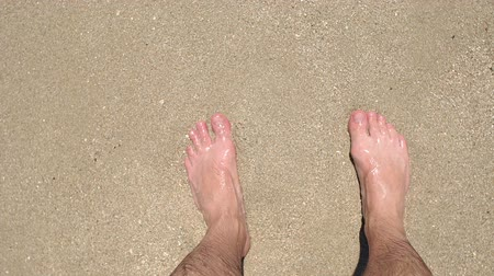 стенд : Close-up of mens feet on the sand in the water at sea, small waves beating against his legs. The view from the top. Стоковые видеозаписи