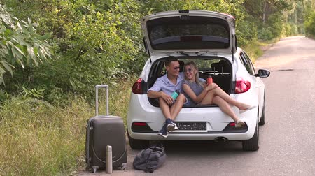 beuta : Loving couple drinks hot tea from thermos flask sitting in car trunk. Happy young couple having a coffee break during road trip in countryside.