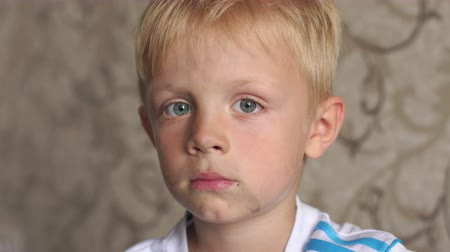 pained : Close-up of a dirty little boys face. The child got dirty playing in the street. Slow motion. Stock Footage