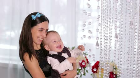 šperk : A caring mother holds her little son in her arms, the baby is dressed in a fashionable shirt with a vest. Close-up of a cheerful blond boy playing with crystals from the chandelier. Happy family. Dostupné videozáznamy