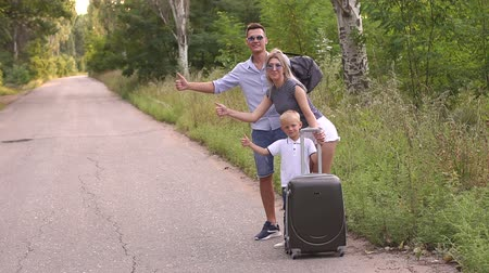 tendo : Family with a child hitchhiking, they stand on the side of the road and catch a car. A family with little son are standing on the side of the road with a suitcase and trying to catch a car. Thumbs up.