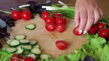 basilico : Close-up woman cuts cherry tomatoes on a wooden cutting board, cucumbers, lettuce, basil lie around. Slow motion.