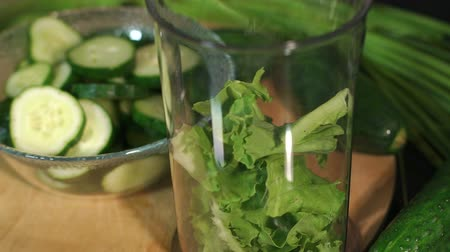 цуккини : Close-up of a girl puts lettuce in a blender bowl for making a smoothie on a black background. Nearby are the ingredients for a healthy cocktail - cucumber, avocado, kiwi, apple.