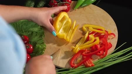 ズッキーニ : Close-up of a woman cutting ripe juicy yellow pepper on a wooden Board, in the background are cucumbers and tomatoes. 動画素材