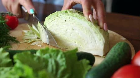 shred : Female hands chopped cabbage on wooden board, close-up. Chopping cabbage with a knife on cutting board.