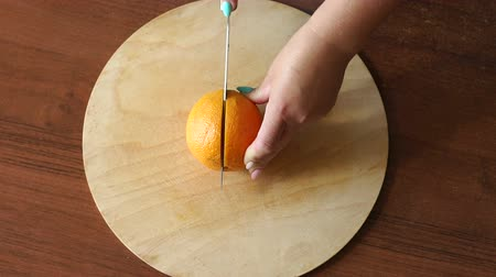 grejpfrut : Hand slicing orange on wooden board. Woman housewife in kitchen at home cutting fresh orange fruits on cutting board. Healthy eating, cooking, dieting and people concept. Wideo