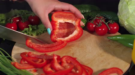 высокое разрешение : Close-up of a woman cutting ripe juicy red pepper on a wooden Board, in the background are cucumbers and tomatoes. High resolution.