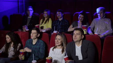 театр : Young people sitting at the cinema, watching a movie and eating pop corn. Close-up. Entertainment and enjoyment concept.