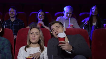 初演 : Couple sitting together in cinema, watching comedy or romantic movie. Handsome guy and beautiful girlfriend sitting near while movie review. Concept of leisure and free time.