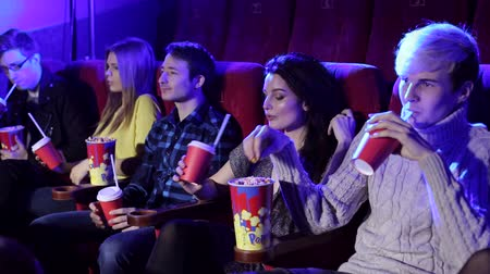 初演 : Cheerful young people watch a movie in a modern cinema. Portrait of a group of young people in a cinema with popcorn and Cola.