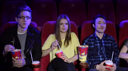 cola : Young fashionable teenagers sit in the cinema and watch a Comedy or a melodrama, eat popcorn and drink Cola. Portrait of smiling teenagers in a modern cinema.