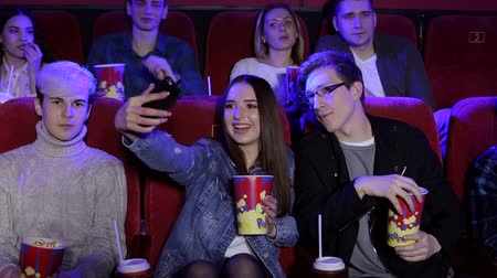 初演 : Two friends making selfie in the cinema. Happy gorgeous young girl taking a selfie with her boyfriend while watching a movie together at the cinema. 動画素材