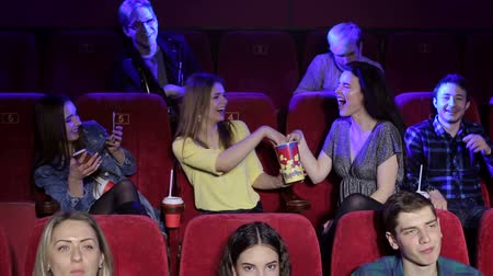 asientos : A group of cheerful young friends throw popcorn at the cinema. Two girls have fun in a movie theater sitting on red chairs, they eat popcorn and throw it. Movies and entertainment concept.