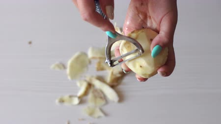 peeler : Close-up of a woman peeling potatoes with a peeler on a white background in the kitchen, high resolution. Woman peeling vegetables using food peeler. Female preparing potatoes before serving.