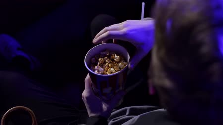 初演 : Close-up of a young man eating popcorn in a movie theater. The guy holds a glass of popcorn in his hands and eats it with pleasure while sitting in a cinema chair. Close-up. 動画素材