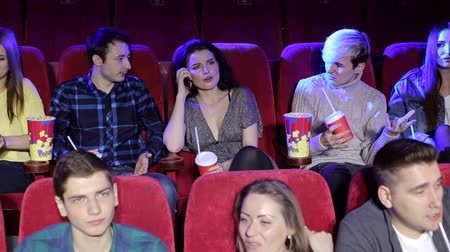 obnoxious : Rude young woman talking on mobile phone while watching movie at the cinema and disturbing audience. The man turns to her and asks her to turn off the phone. Stock Footage