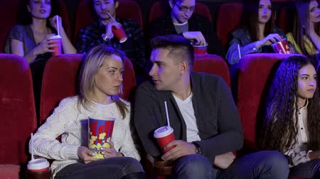 初演 : Happy young couple in love sitting in a movie theater in comfortable red chairs and watching a fun movie. Positive couple drinking cola and eating popcorn in cinema. A cinema full of people.