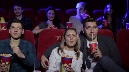 初演 : Close-up of teenagers sitting in red chairs in the cinema and watching a movie, in the background sits a lot of people. Young happy people relax in the cinema, eat popcorn and drink soda.