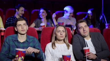 初演 : A group of young people sit in a cinema with popcorn and drinks and watch a funny comedy film, they laugh. Young friends stylish girls and boys watching new movie at cinema, spending time together. 動画素材