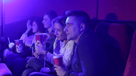 初演 : Young people sitting at the cinema, watching a movie and eating pop corn. Close-up. Entertainment and enjoyment concept. Young guys relax in the cinema with popcorn and drinks. 動画素材