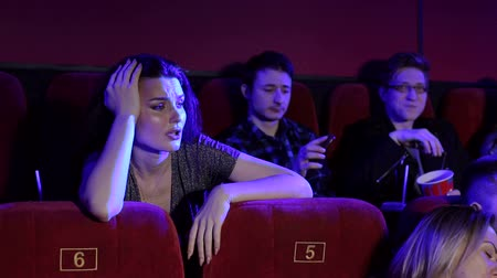 初演 : Young people watch a boring movie in the cinema. Portrait of a group of young people in the cinema. A couple in love, teenagers and a group of friends relax in the cinema with popcorn and drinks.