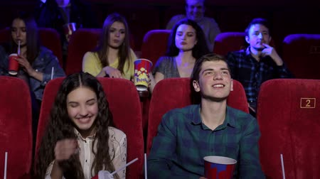 初演 : A cheerful young couple throw popcorn at the cinema. A guy and a girl have fun in a movie theater sitting on red chairs, they eat popcorn and throw it. Movies and entertainment concept. 動画素材