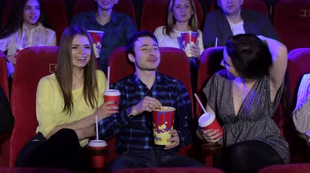 初演 : Close-up of funny teenagers resting in the cinema, they watch Comedy and eat popcorn. Friends watching movie and smiling together, entertainment and enjoyment concept. 動画素材