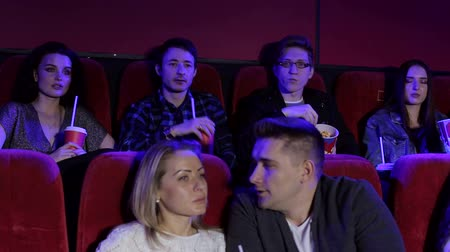 infastidito : Two men are fighting in the cinema, their girls are trying to calm their guys. A group of young people quarrel in the cinema, they throw popcorn at each other.