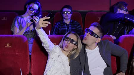 初演 : Happy young couple taking a selfie while watching a movie together at the cinema. Happy couple in 3D glasses watching a movie and taking selfies.