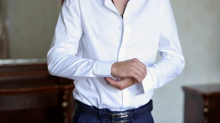 mandzsetta : Businessman buttoning buttons on shirt sleeves, close-up. A successful man in a white shirt fastens buttons on the sleeves, close-up.