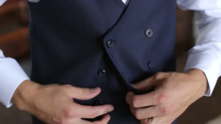manşet : A man fastens buttons on a vest from a three-piece suit. Businessman puts on a jacket. Stok Video