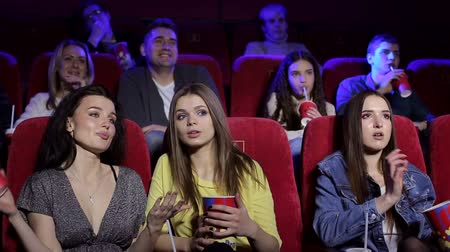 初演 : Portrait of a group of young people in the cinema. A couple in love, teenagers and a group of friends relax in the cinema with popcorn and drinks.