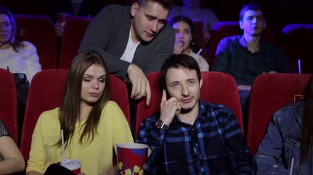 obnoxious : A man talking on the phone sitting in a movie theater while watching a movie, an irritated man makes him a remark. Ill-mannered man talking on the phone in the cinema and interfere with other visitors