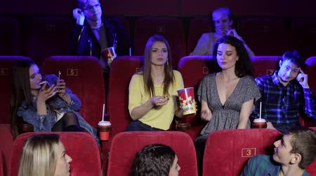 asientos : A group of cheerful young friends throw popcorn at the cinema. Three girlfriends have fun in a movie theater sitting on red chairs, they eat popcorn and throw it. Movies and entertainment concept. Archivo de Video