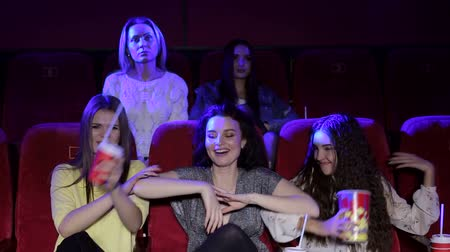 ilginç : Funny girls friends at the cinema watching a movie together and eating popcorn, entertainment and enjoyment concept. Young people sitting at the cinema.