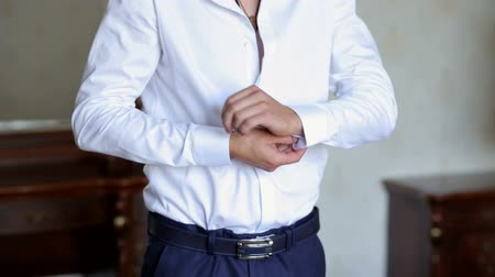 hand cuffs : Businessman buttoning buttons on shirt sleeves, close-up. A successful man in a white shirt fastens buttons on the sleeves, close-up.