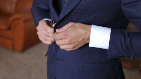 mandzsetta : A man buttoning his jacket, close-up. A successful young man puts on a suit jacket in the morning. Businessman puts on a jacket.