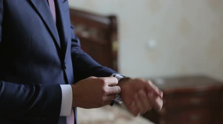 mandzsetta : Close-up of a successful man is putting on a wristwatch. Mens hand with a watch, watch on a mans hand, putting the clock on the hand.