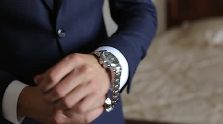 manşet : Close-up of a successful man is putting on a wristwatch. Mens hand with a watch, watch on a mans hand, putting the clock on the hand.