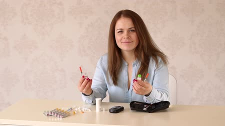 yüksek çözünürlüklü : A young diabetic woman learns to type insulin into a syringe on her own. Close-up of insulin, glucometer, syringes and insulin syringe pens on the table. Stok Video