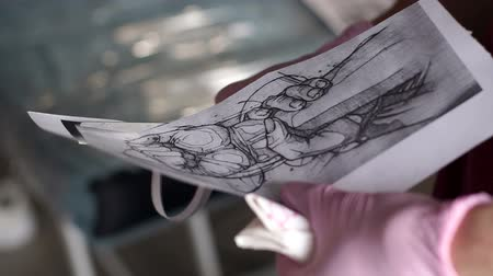 kár : Tattoo master cuts out a picture with scissors to apply it to the skin of the client in the tattoo parlor. The process of tattooing on the skin.