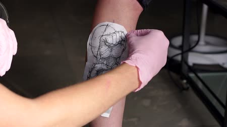 bras homme : Tattoo artist puts a picture on a young womans leg, the process of creating a tattoo. Man doing picture on a leg of man. Tattooist makes a tattoo. Close-up.