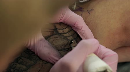 bras homme : Close-up of a tattoo artist doing a tattoo on the girls leg, he fills with a black ink outline of a tattoo. Slow motion. Close-up of a tattoo machine with black ink. Vidéos Libres De Droits