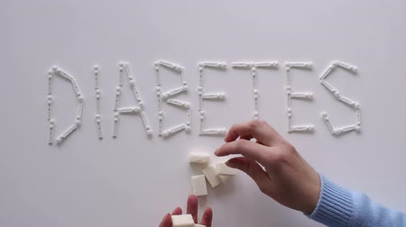 glicose : The word DIABETES with lancets for glucometer on the table on a white background. Lay next to the sugar cubes. A womans hand takes a sugar cube. The concept of type 1 and type 2 diabetes.