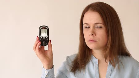 cukorbaj : A young diabetic girl is holding a blood glucose meter with a high blood sugar level. Theme of diabetes. High blood glucose levels. Diabetes type 1. Slow motion. Portrait. Stock mozgókép