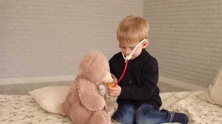テディベア : A cute little boy is playing at home in the bedroom with a Teddy bear, he listens to breathing with a toy stethoscope. Health Care. Heart stethoscope. Little doctor examining teddy bear in white room.